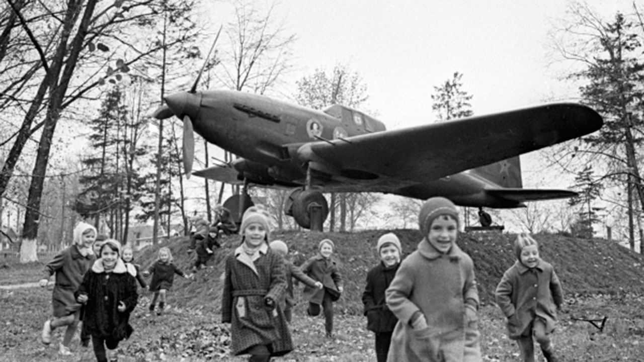 Дети играют возле установленного на постаменте штурмовика ИЛ-2