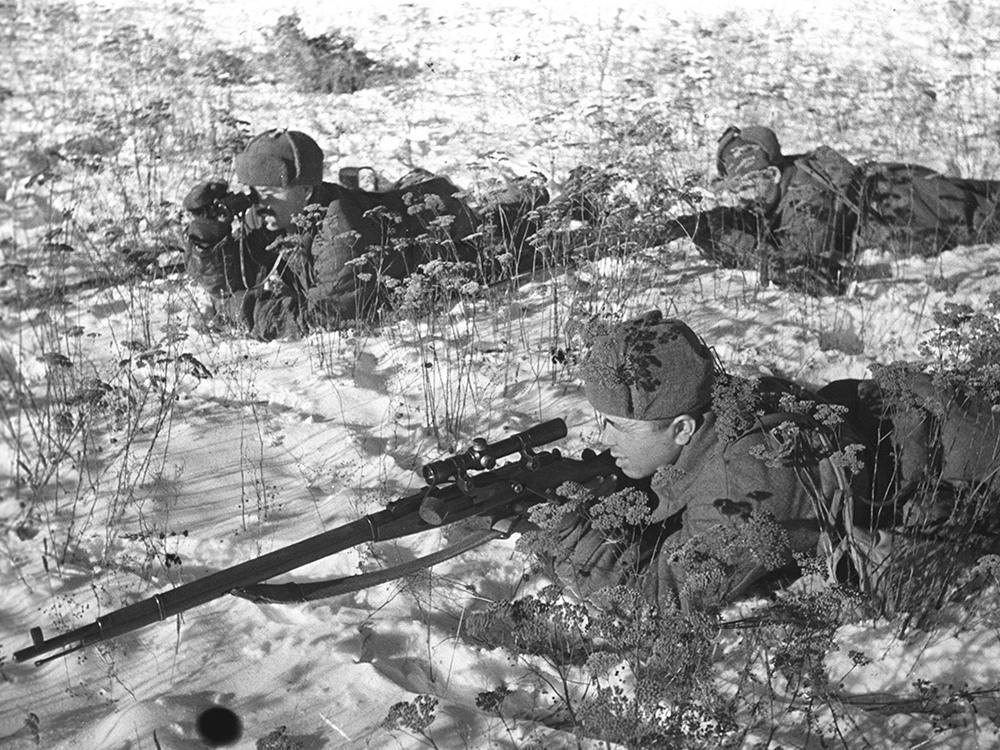 Советский снайпер в плащ-накидке со снайперской винтовкой Мосина, оснащенной оптическим прицелом ПЕ.
